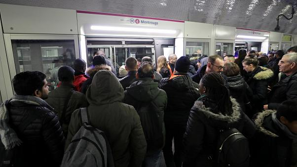 Commuters wait to board a train at the Gare du Nord metro station in Paris