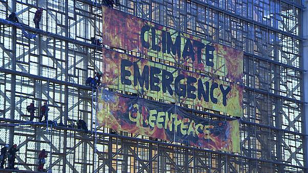 Greenpeace hang Climate Emergency banner at new EU headquarters