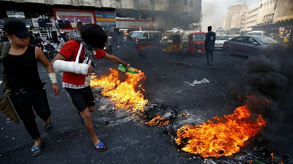تعدادی معترض عراقی مرد مسلح را کشتند و از تیرک چراغ راهنمایی آویزان کردند