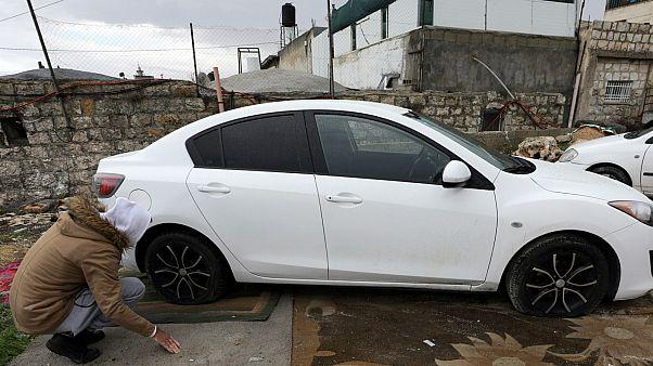 رجل فلسطيني يتفقد إطارات سيارته بعد حملة تخريب في شعفاط القدس الشرقية- أرشيف رويترز