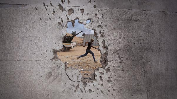 Libya'da Kaddafi güçlerine karşı savaşan muhalif bir savaşçı kendi cephesine koşarken / 2011 (arşiv)