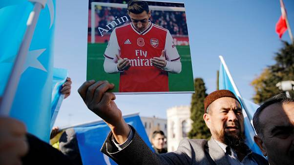 متظاهرة داعم لمسلمي الأيغور يحمل صورة أوزيل