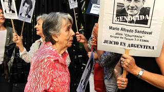 Beatriz Cantarini de Abriata, mother of Hernan Abriata stands next to a portrait of former Argentine police officer Mario Sandoval