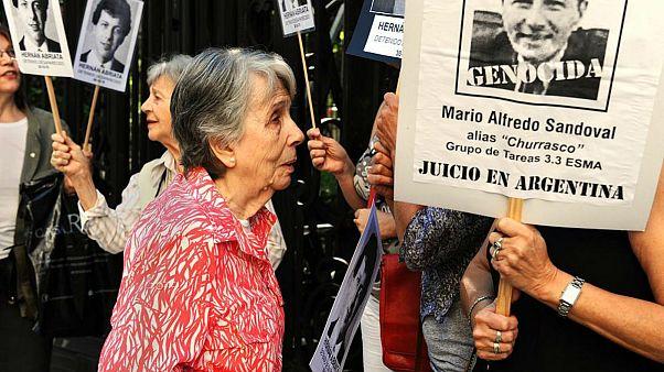 بئاتریس کانتارینی، مادر ۹۲ ساله هرنان آبریاتا در کنار پلاکاردی که تصویر ماریو ساندووال روی آن نصب است