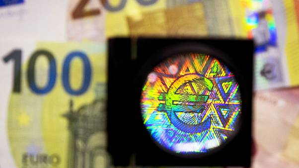 A loupe enlarges one of the security features of the new 100 and 200 Euro notes.
