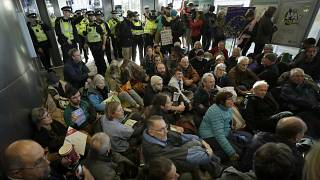 Police Officers stand guard as Extinction Rebellion demonstrators peacefully block an entrance to City Airport in London, Thursday, Oct. 10, 2019.