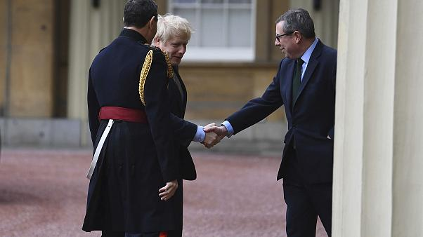 Prime Minister Boris Johnson is greeted by the Queen's Equerry-in-Waiting Lieutenant Colonel Charles Richards (left) and her private secretary Edward Young.