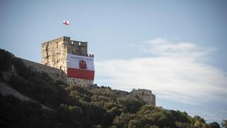 """A Gibraltar flag reading """"self determination is our right"""" is displayed on a castle and old jail during National Day celebrations in the British territory of Gibraltar in 2019"""