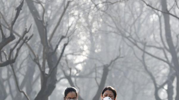 Deux femmes se protègent avec un masque, décembre 2016, à Pékin, Chine