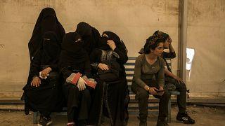 نساء مرتبطات بمقاتلي جماعة الدولة الإسلامية يجلسن بجانب حارسات من قوات سوريا الديمقراطية في مخيم الهول يونيو 2019