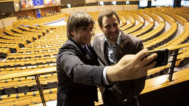 Carles Puigdemont, left, and Antoni Comin take a selfie at the European Parliament