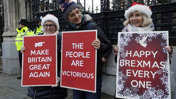 Pro Brexit demonstrators hold banners outside Parliament in London, Friday, Dec. 20, 2019.