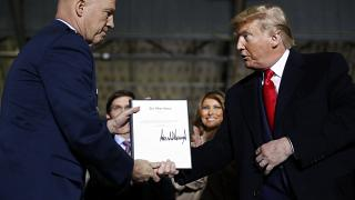 President Donald Trump shakes hands with General Jay Raymond after signing letter appointing him to the U.S. Space Command