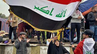 متظاهرة عراقية ترفع العلم في بغداد الأسبوع الفائت