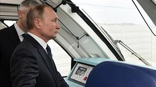 Vladimir Putin rides a train across the new bridge linking Russia and the Crimea