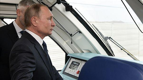 Vladimir Putin rides a train across the new bridge linking Russia and the Crimea