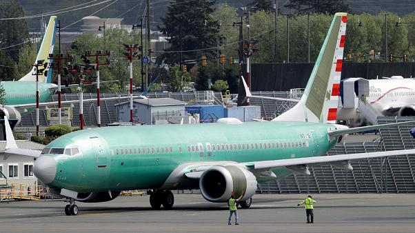 Workers stand near a Boeing 737 MAX built for American Airlines