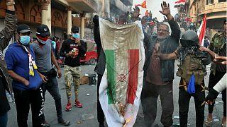 متظاهر عراقي يحرق العلم الإيراني في بغداد