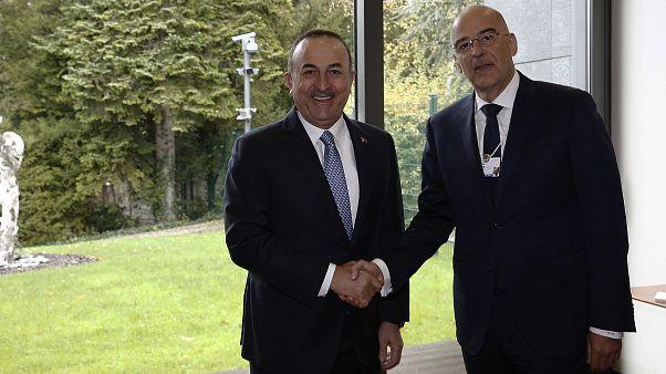 Ο υπουργός Εξωτερικών της Ελλάδας Νίκος Δένδιας ανταλλάσσει χειραψία με τον Τούρκο ομόλογό του Μεβλούτ Τσαβούσογλου στο περιθώριο του Παγκόσμιου Οικονομικού Φόρουμ