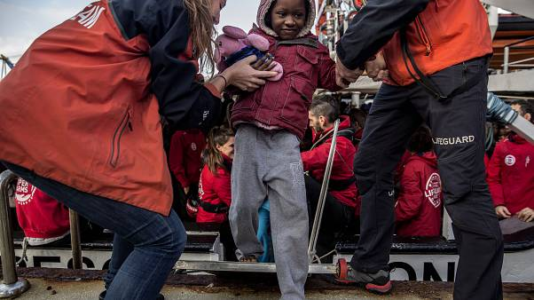 A migrant child is helped from the Spanish NGO Proactiva Open Arms rescue vessel, after being rescued Dec. 21, in the Central Mediterranean Sea.