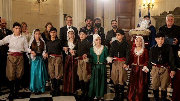 Το πρωθυπουργικό ζεύγος και η κόρη τους, ακούν τα χριστουγεννιάτικα κάλαντα από  τους Σύλλογους Ασιγωνιωτών «Παύλος Γύπαρης» και Ένωση Κρητών «Άγιος Ανδρέας Κρήτης»