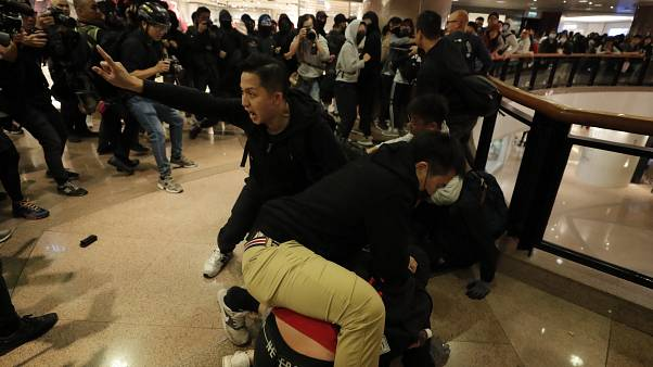 Plainclothes police officers arrest protesters in a Hong Kong mall.