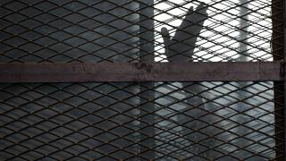 In this Aug. 22, 2015 file photo, a Muslim Brotherhood member waves his hand from a defendants cage in a courtroom in Torah prison, southern Cairo, Egypt.
