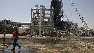 عامل يمشي أمام حقل خريص النفطي في خريص في السعودية