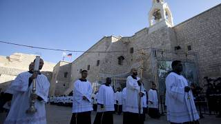 Clergymen attend Christmas celebrations outside the Church of the Nativity, on Christmas Eve, in the West Bank City of Bethlehem