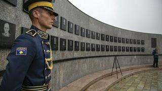 ضابط يقف مستعدا أمام نصب تذكاري لضحايا حرب الكوسوفو
