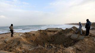 فلسطينيون يتفقدون موقع ضربة جوية إسرائيلية في جنوب قطاع غزة
