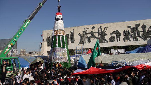 متظاهرون يعملون على تركيب شجرة ميلاد في ساحة التحرير في بغداد تحمل صور ضحايا المظاهرات 24 ديسمبر 2019