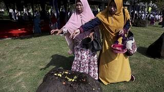Women sprinkle flowers on a stone marking the mass grave for the victims of 2004 tsunami, during a commemorative service in Banda Aceh, Indonesia, Dec. 26, 2018.