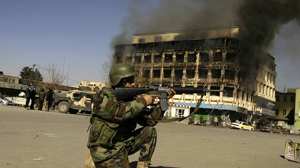 An Afghan police officer aims his weapon at the scene of attack in central Kabul, Afghanistan, Monday, Jan. 18, 2010 (AP Photo/Ahmad Massoud)