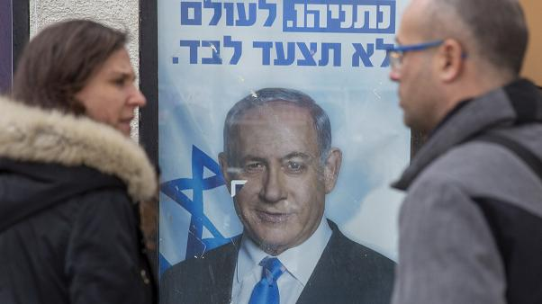 People look at a poster of Israel's Prime minister and governing Likud party leader Benjamin Netanyahu.