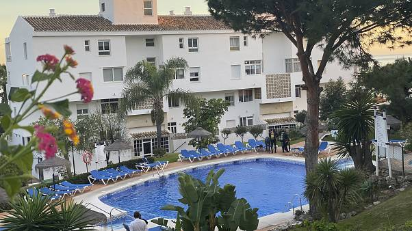 In this photo taken on Tuesday Dec. 24, 2019, Civil guard divers, right, work at the side of a swimming poo at the Club La Costa World holiday resort near Malaga, Spain.