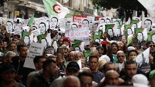 متظاهرون جزائريون يرفعون صور محتجزين