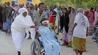 A civilian who was wounded in the Mogadishu suicide car bomb attack is helped