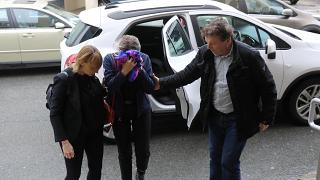 A British woman, accused of lying about being gang raped, covers her face as she arrives at the Famagusta courthouse in Paralimni.