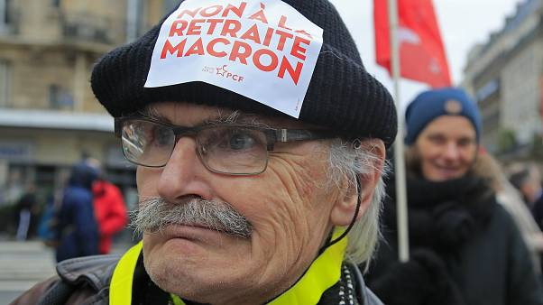 """A demonstrators wears a sticker on his hat that reads, """"no to Macron's pension reform during a protest in Paris, Saturday, Dec. 28, 2019."""