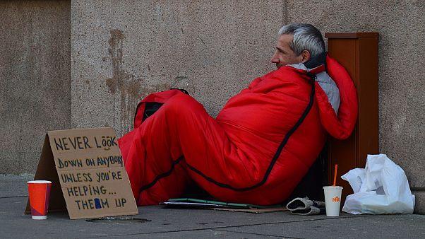 """Obdachloser mit einem Schild """"Schau nie auf jemanden herab, es sei denn, du hilfst ihm, aufzustehen"""""""