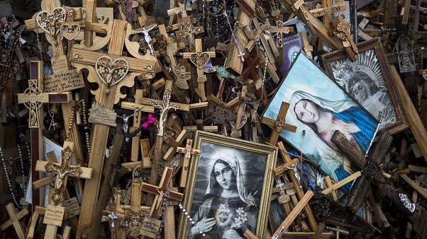 In this photo taken on Wednesday, July 17, 2019, crosses, rosaries and portraits of the Virgin Mary are displayed, at the Hill of Crosses a Lithuanian national pilgrimage site