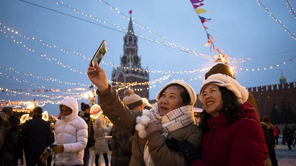 Tourists take a selfie in Red Square decorated for New Year celebrations, with the the Kremlin's Spasskaya Tower in the background, in Moscow, Russia.