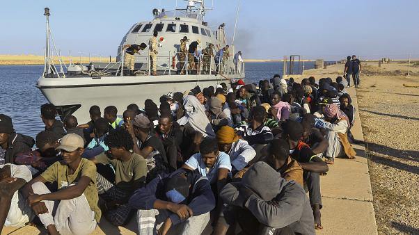 مهاجرون تم إنقاذهم يجلسون قرب قارب تابع لخفر السواحل في مدينة خومس، ليبيا، 1 أكتوبر 2019