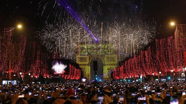 Revellers photograph fireworks over the Arc de Triomphe as they celebrate the New Year on the Champs Elysees, in Paris, France, Wednesday, Jan. 1, 2020.