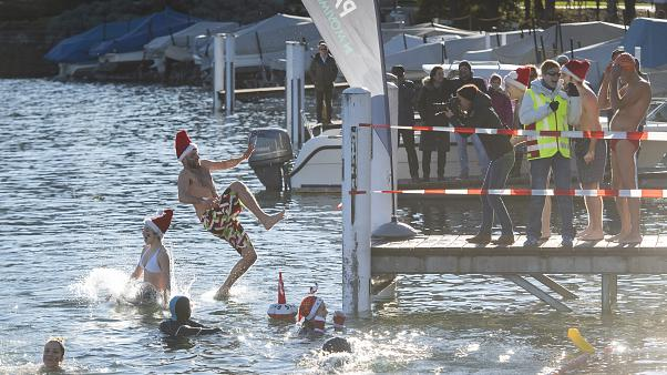 Participants of the annual winter swimming jump into the Lake Lugano on St Stephen's Day in Paradiso, Switzerland, Thursday, Dec. 26, 2019.
