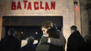 In this Nov. 13, 2016 file photo, women hug in front of the Bataclan concert hall in Paris, as France marked the anniversary of Islamic extremists' coordinated attacks.