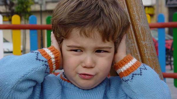Kulaklarını tıkayan bir çocuk