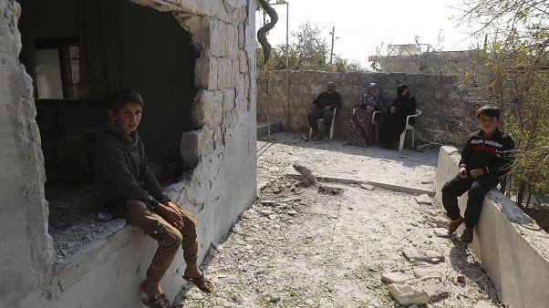طفال يجلسون بجوار منزلهم المدمر في قرية بريشا في محافظة إدلب، سوريا 2019