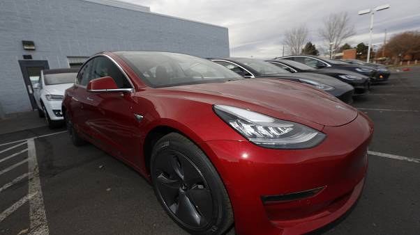 In this Sunday, Nov. 10, 2019, photograph, a long row of unsold 2020 Model 3 sedans sits at a Tesla dealership in Littleton, Colo. (AP Photo/David Zalubowski)